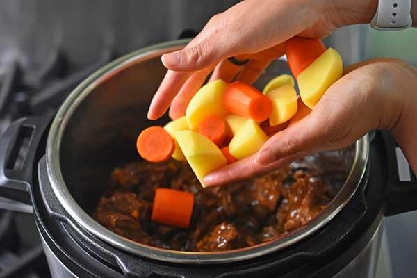 cho khoai tây và cà rốt vào ninh