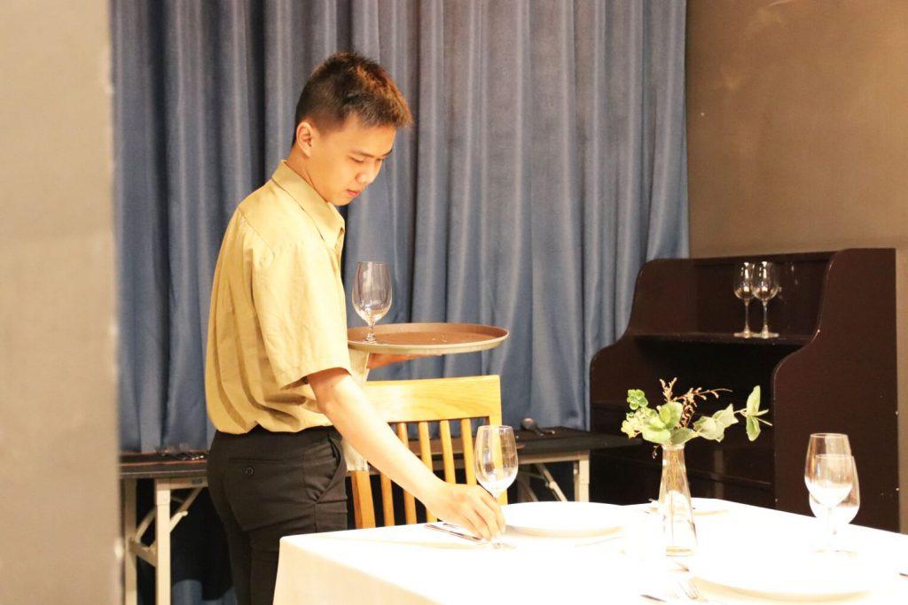 hình ảnh sinh viên CET thực hành cách bố trí bàn trong nhà hàng khách sạn